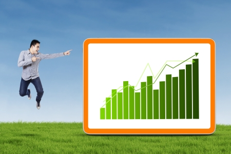 Asian businessman jumping and pointing a graph on the board photo