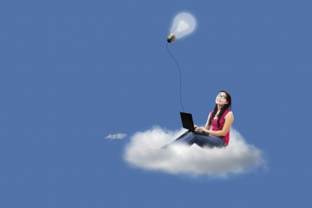 Asian female sitting on cloud with laptop under lit lightbulb Stock Photo - 23521025