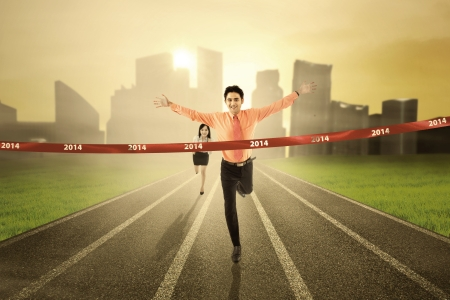 finish: Business competition concept: Businessman crossing the finish line on the track