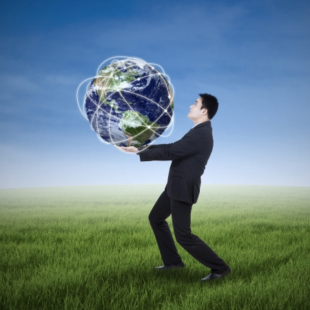 businessman carrying a globe: Asian businessman carrying a globe on the meadow Stock Photo