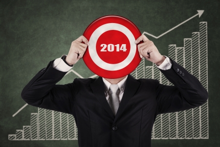 Businessman holding a target board with year 2014 writing in the middle