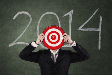 Businessman holding a target board with year 2014 on the chalkboard photo