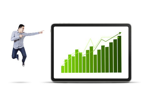 Young asian businessman jumping and pointing at the business chart photo