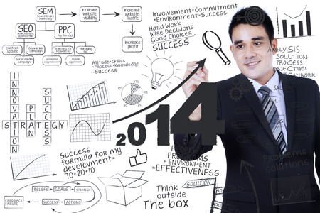 Smiling businessman writing a business concept on transparent whiteboard photo