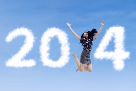 Excited asian businesswoman is jumping with new year 2014 on the sky photo