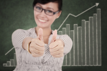 Happy businesswoman showing thumbs up with growth graph on chalkboard photo