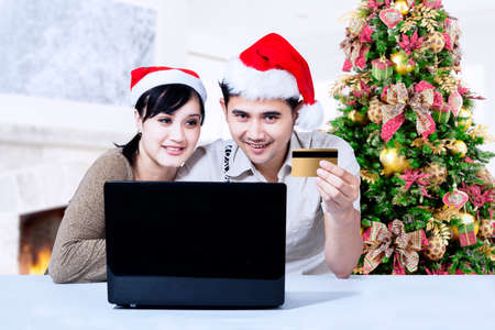 Young couple in Christmas online shopping at home photo