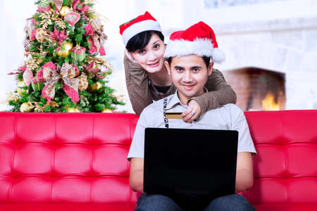 Couple doing online shopping during Christmas at home photo