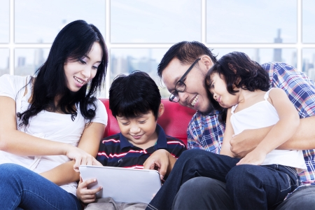 Family enjoying quality time at apartment by using touchpad photo