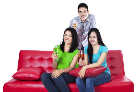 Happy three teenagers with champagne, isolated on white background photo
