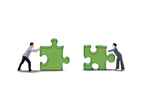 Business partner putting together two puzzle pieces - isolated on white background photo