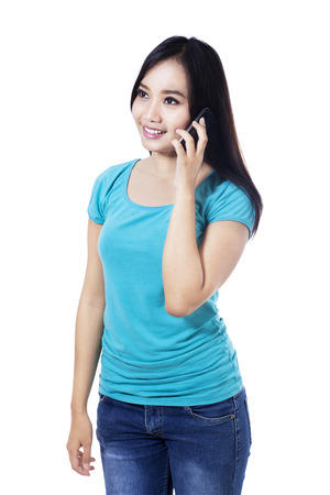 filipino adult: Portrait of smiling woman talking on phone, isolated on white background Stock Photo