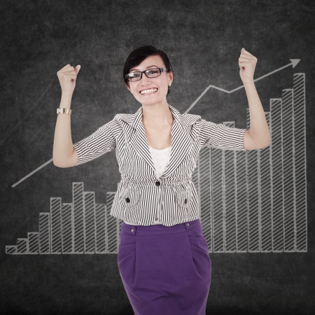 Successful businesswoman with arms up on financial charts photo