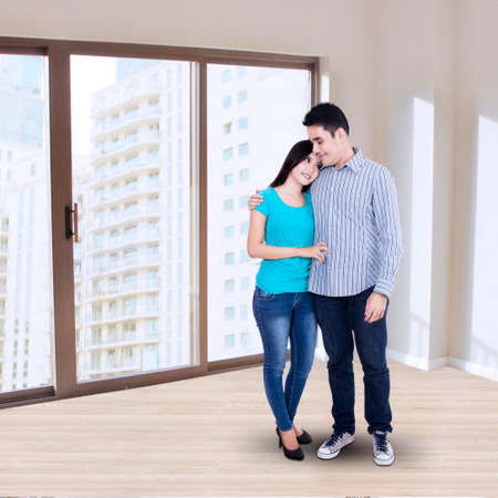 Full length of lovely young couple at the new home photo