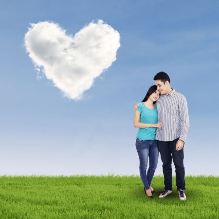 Young couple standing under clouds shaped of heart on the grass photo