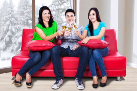 Group of young people toast champagne at home photo