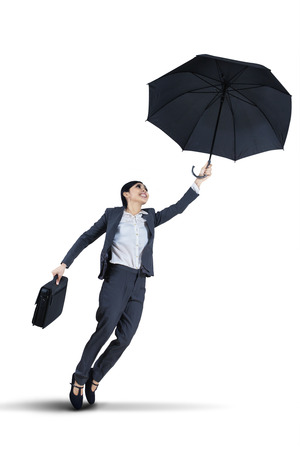 flying woman: Businesswoman flying away from her business problems with an umbrella Stock Photo