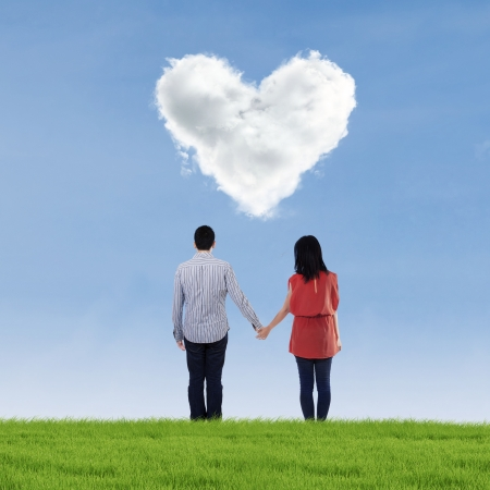 Young couple standing on the meadow with clouds shaped of heart photo