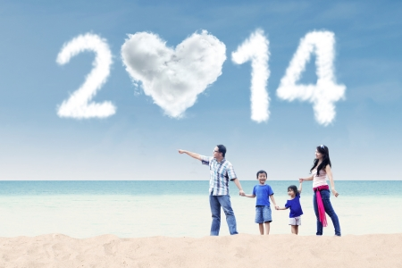 Happy family having fun in the beach with heart shaped cloud of new year 2014 Stock Photo - 23574210