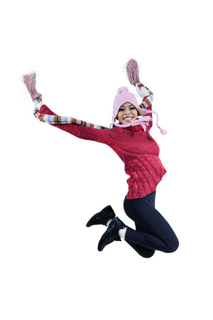 filipino adult: Beautiful woman in winter clothing jumping on white background