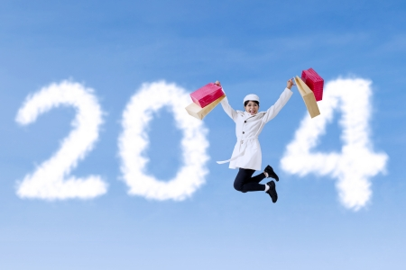 Asian woman with shopping bag is jumping announce Happy New Year 2014 photo