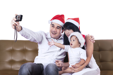 Christmas family take a photo sitting on brown sofa photo