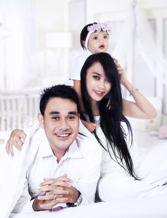 Happy couple with their baby playing on the bed at home photo