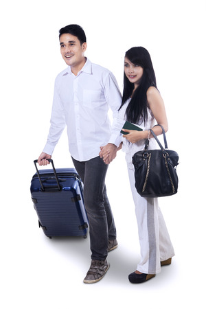 Smiling couple with suitcase on a white background photo