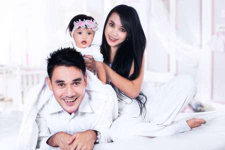 is playful: Familia feliz con el bebé jugando en la cama en su casa