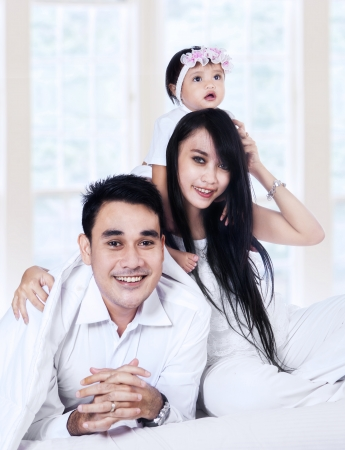 Happy family with baby playing on the bedroom photo