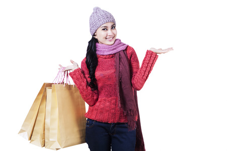 Happy teenage girl in winter clothes with shopping bags photo