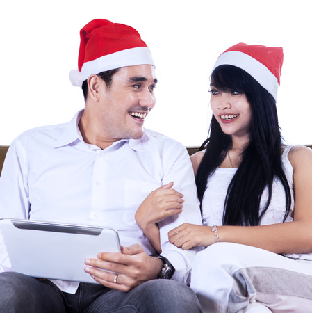 Christmas couple using a digital tablet isolated on white background photo