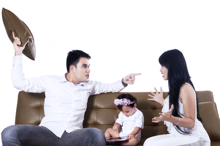 Parents arguing in front of their daughter isolated on white photo