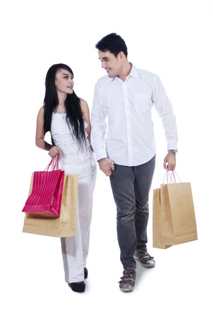 Romantic young couple carrying shopping bags isolated on white background  photo