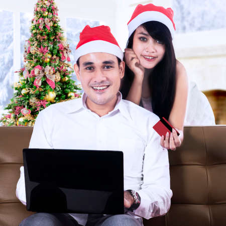 Happy smiling couple using credit card to shopping online photo