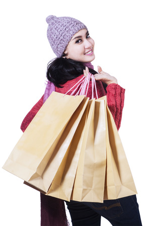 Smiling woman carrying shopping bags isolated on white background photo