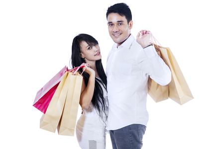 Young couple holding many shopping bags isolated on white photo