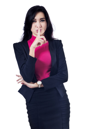 hushed: Beautiful businesswoman making a silence gesture. Isolated on white background Stock Photo