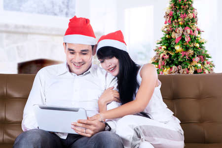 Portrait of happy christmas couple with digital tablet at home photo