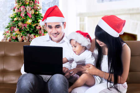 Happy christmas family using a laptop at home photo