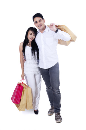 Happy couple with shopping bags - isolated on white background photo