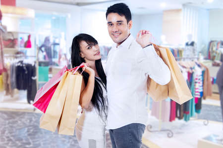 Happy couple with shopping bags in the shopping center photo