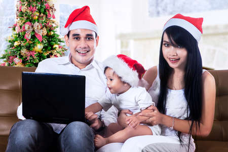 Happy family in santa hats playing with a laptop at home photo