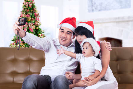 Happy family in Santa hat taking a photo with camera photo