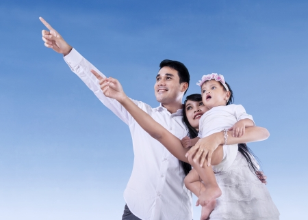 Happy family pointing at blue sky outdoors photo