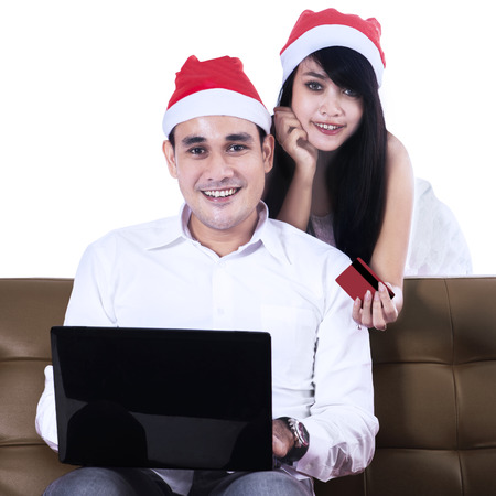 Smiling christmas couple shopping online with credit card and laptop photo