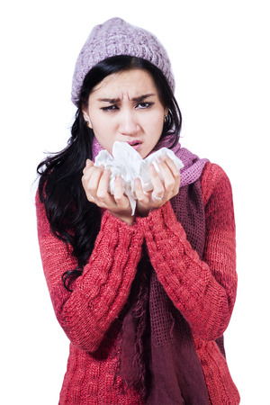 Portrait of sneezing woman with handkerchief on white  photo