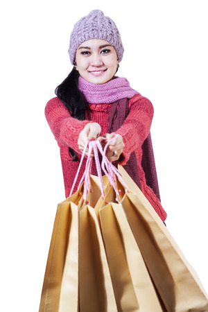 Winter woman holding shopping bags isolated on white background photo