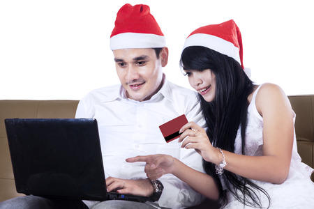 Smiling young couple buying christmas gift online photo
