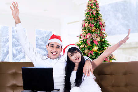 Happy young couple buying christmas gift online at home photo